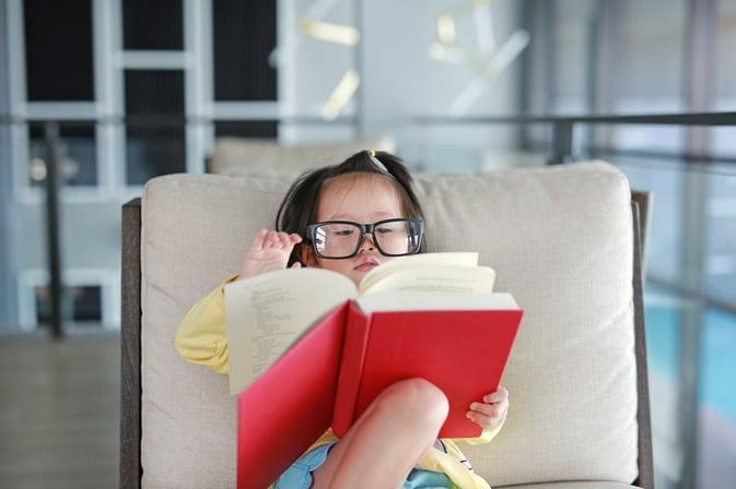 Barn med briller som leser bok. Geniet i barnehagen.